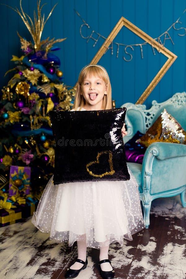 Menina de sorriso com um descanso contra o fundo da árvore de Natal imagem de stock