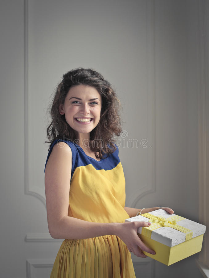 Menina de sorriso com um presente fotografia de stock royalty free