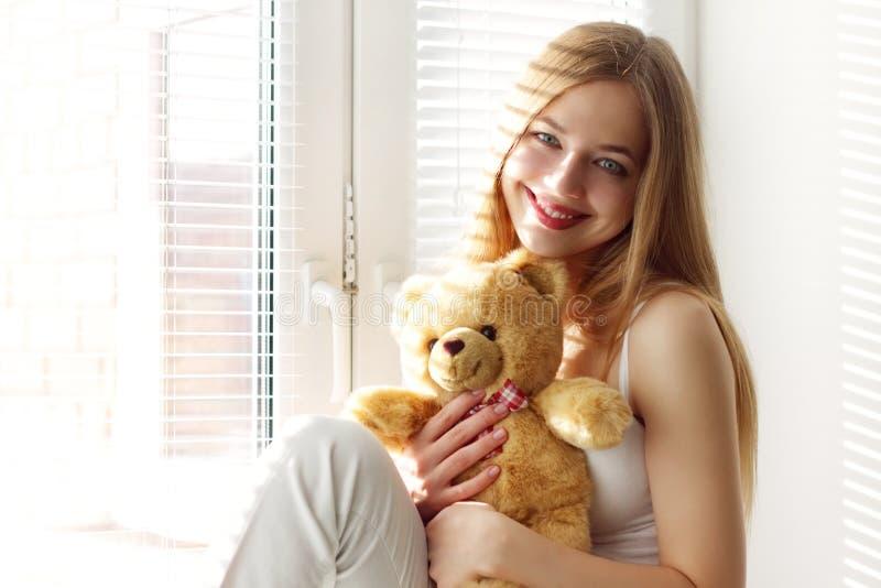 Menina de sorriso com um urso de peluche fotos de stock royalty free
