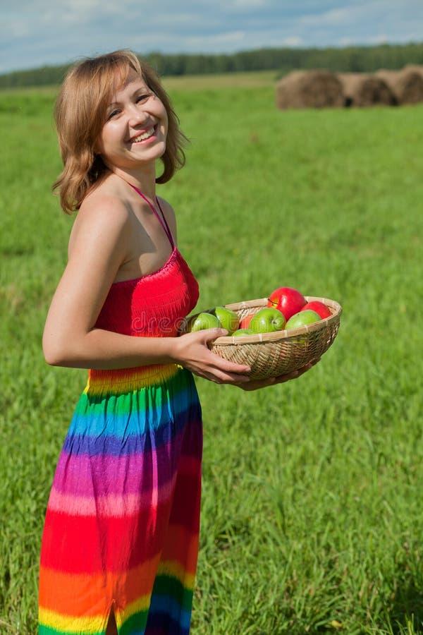 Menina de sorriso com uma cesta das maçãs foto de stock royalty free