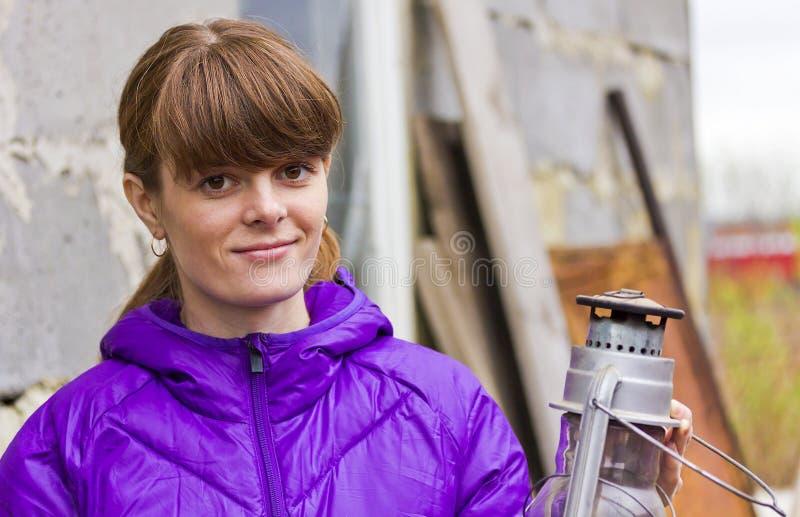 Menina de sorriso com uma lâmpada de querosene velha fotografia de stock