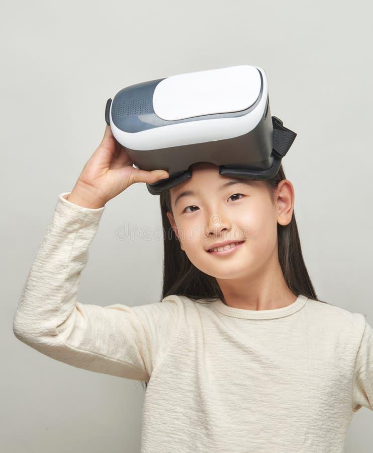Menina de sorriso com vidros da realidade virtual foto de stock