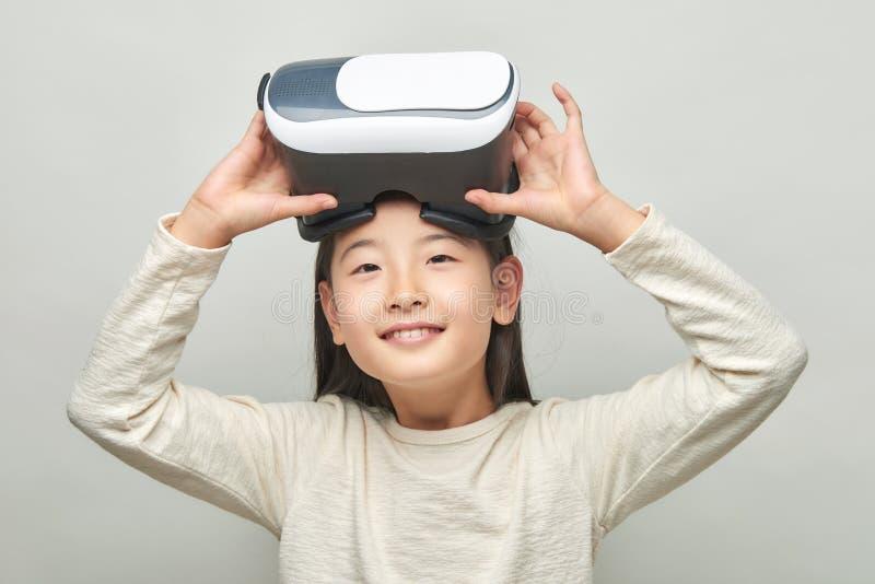 Menina de sorriso com vidros da realidade virtual fotos de stock
