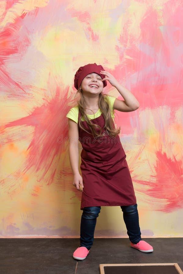 A menina de sorriso cozinha o levantamento no chapéu e no avental do cozinheiro chefe imagem de stock