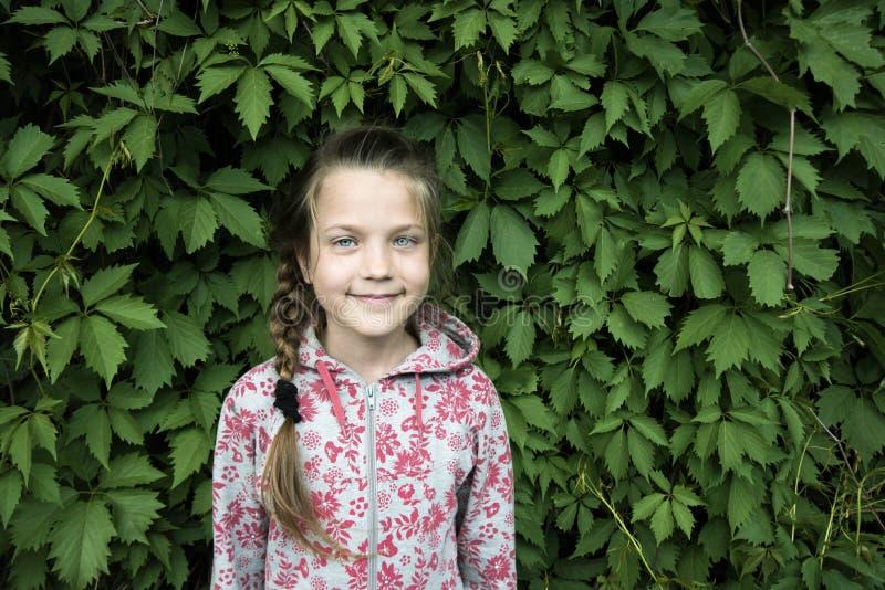 Menina de sorriso da criança nas folhas fotografia de stock royalty free