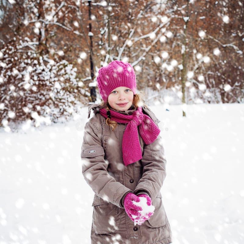 Menina de sorriso da criança que joga com neve no parque do inverno imagem de stock