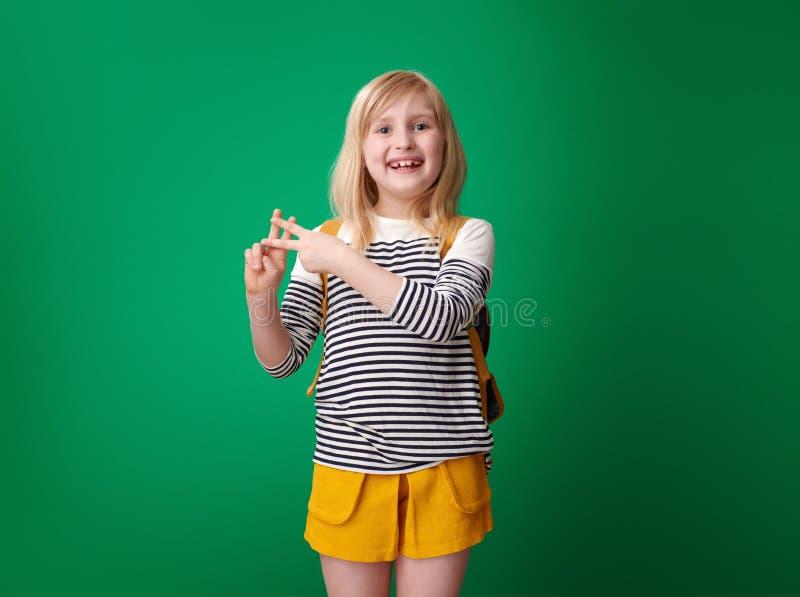 Menina de sorriso da escola que mostra o gesto do hashtag no fundo verde fotografia de stock royalty free