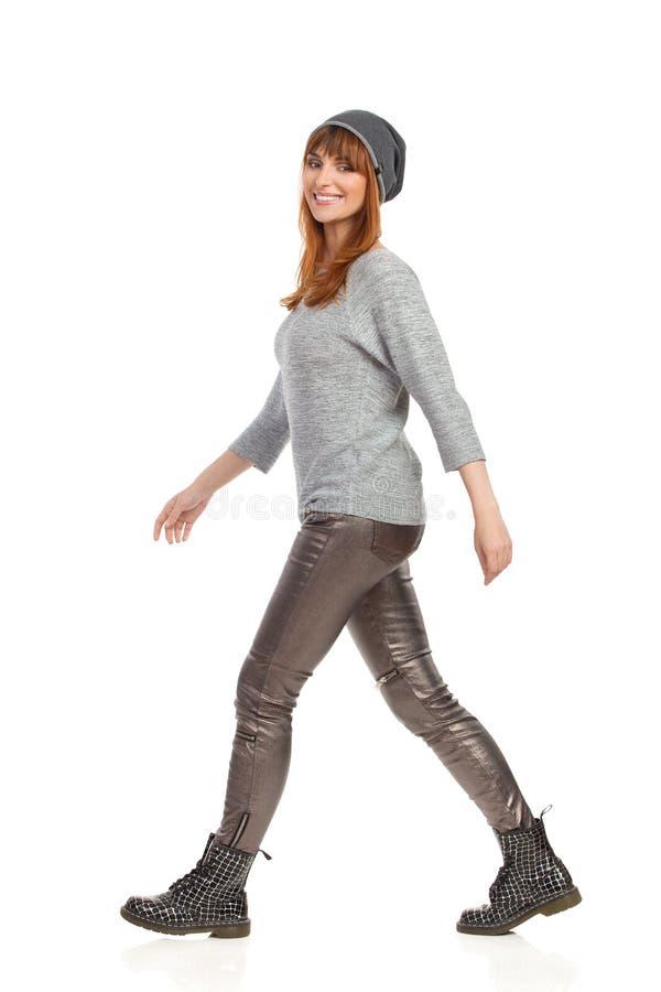 A menina de sorriso da jovem mulher no tampão do inverno é de passeio e de vista a câmera fotografia de stock royalty free