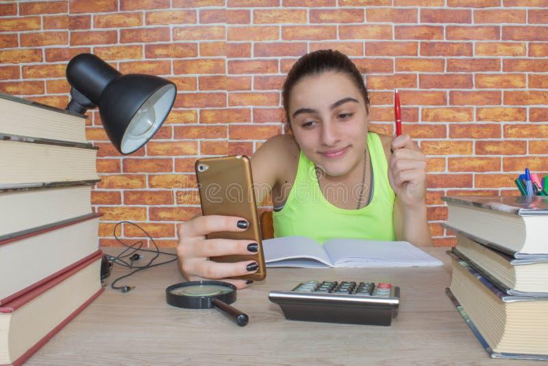 Menina de sorriso do adolescente que faz trabalhos de casa na tabela em casa Estudante com a pilha dos livros e das notas que est fotografia de stock royalty free