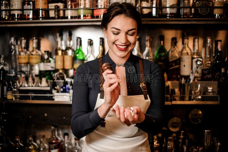 Menina de sorriso do barman que quebra um cubo de gelo imagens de stock royalty free