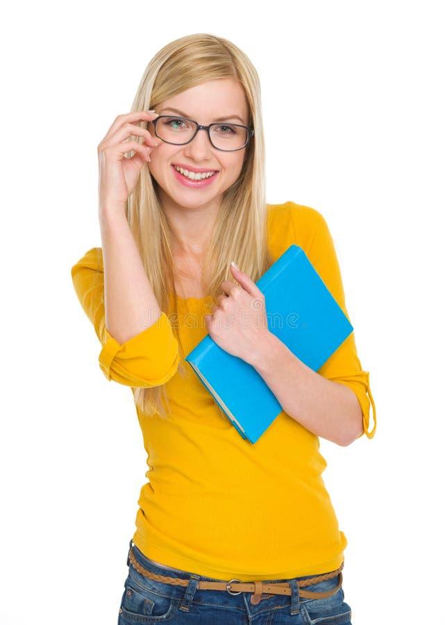 Menina de sorriso do estudante nos vidros com livro imagem de stock
