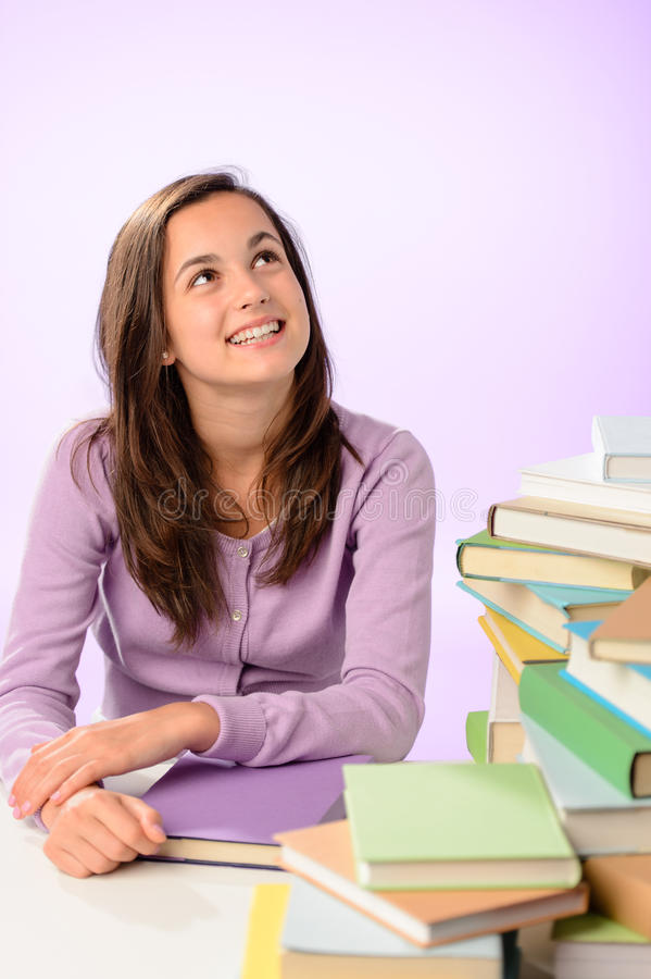 Menina de sorriso do estudante que olha acima o fundo roxo foto de stock