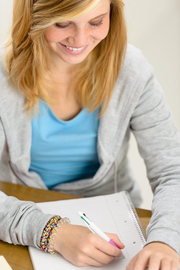 Menina de sorriso do estudante que olha a escrita no papel foto de stock