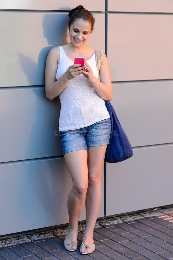 Menina de sorriso do estudante que usa a faculdade do telefone celular fotos de stock