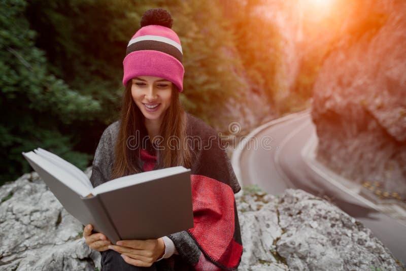 A menina de sorriso do moderno é livro de leitura nas montanhas imagens de stock