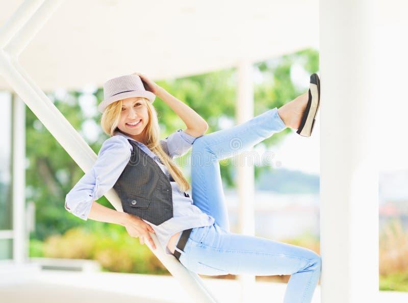 Menina de sorriso do moderno que senta-se na estrutura urbana imagem de stock royalty free