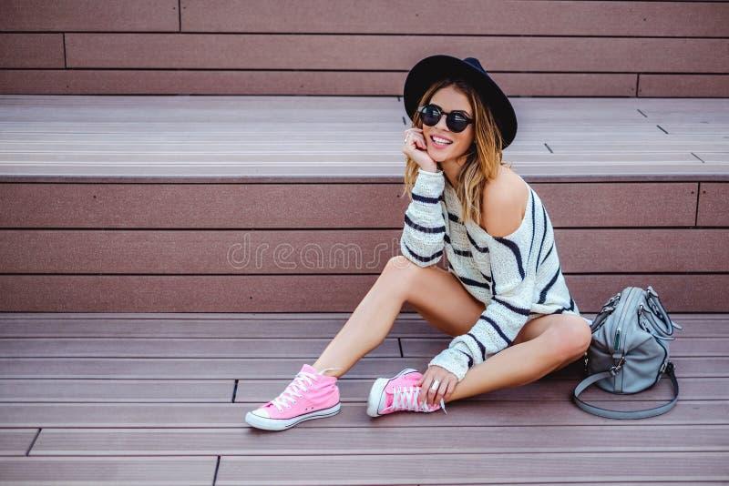 Menina de sorriso do moderno que senta-se nas escadas fotos de stock royalty free