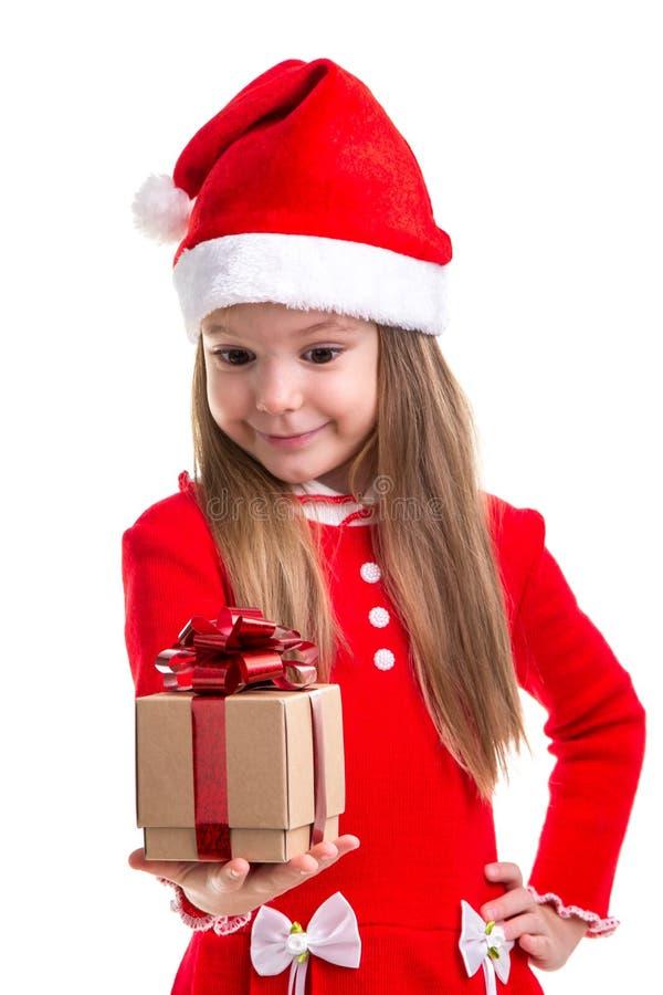 Menina de sorriso do Natal que olha o presente que guarda o na mão, vestindo um chapéu de Santa isolado sobre um fundo branco imagens de stock royalty free