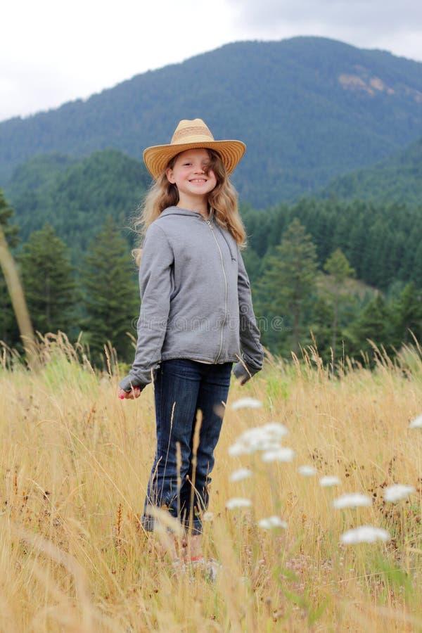 Menina de sorriso do país que está no campo imagem de stock