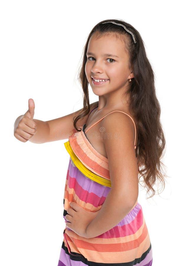 A menina de sorriso do preteen mantém seu polegar fotos de stock