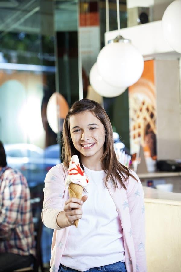 Menina de sorriso do Preteen que guarda o creme de Vanilla Ice na sala de estar imagem de stock royalty free