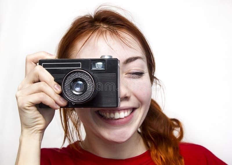 Menina de sorriso do ruivo com camer velho imagem de stock