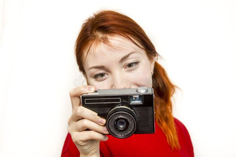 Menina de sorriso do ruivo com camer velho fotos de stock royalty free