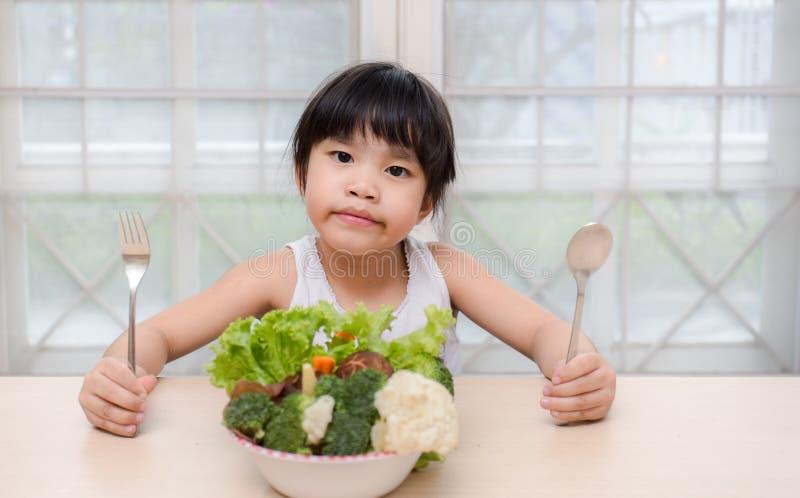A menina de sorriso doce bonito nova pequena come a salada fresca/conceito saudável comer imagem de stock royalty free