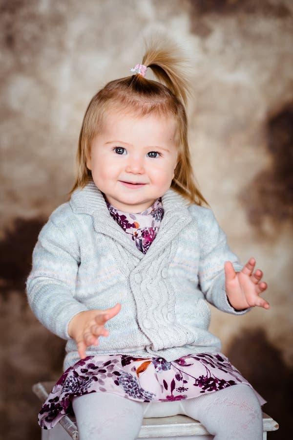 Menina de sorriso doce com o cabelo louro que senta-se na cadeira foto de stock royalty free
