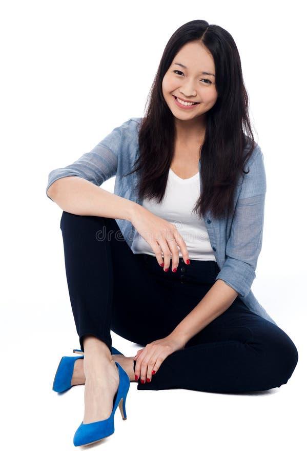 Menina de sorriso elegante que senta-se no assoalho imagem de stock