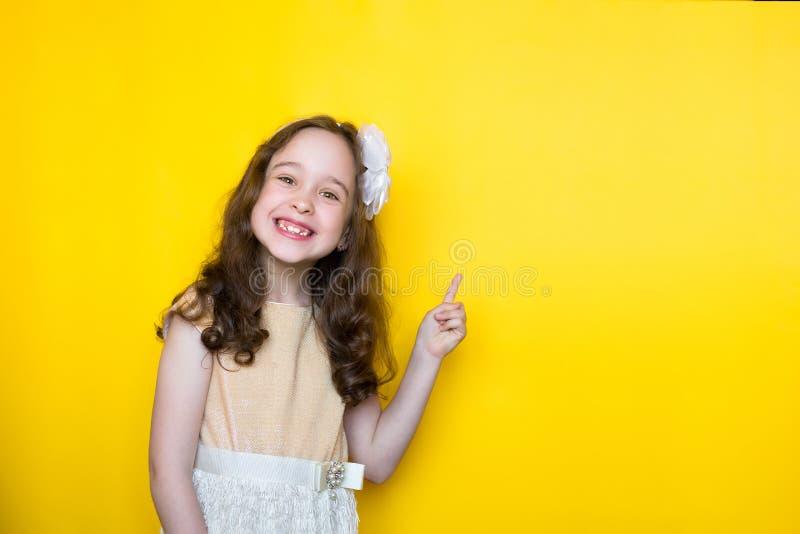 Menina de sorriso em pontos amarelos do fundo seu dedo no espa?o para rotular Conceito da instru??o imagens de stock royalty free