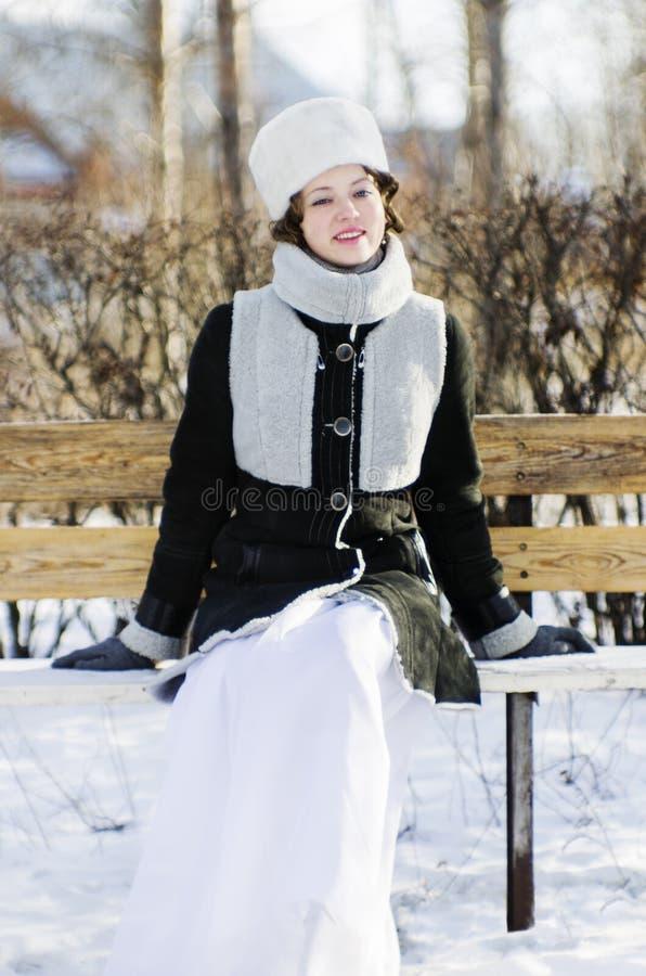 A menina de sorriso em um banco no inverno estaciona imagem de stock