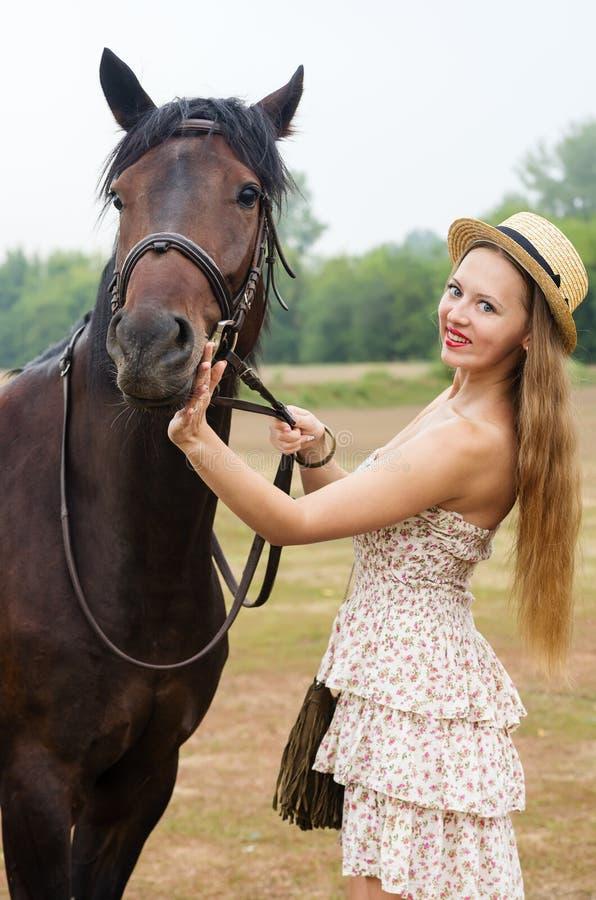 Menina de sorriso em um chapéu de palha e em um vestido do verão, fotografados com um cavalo imagens de stock