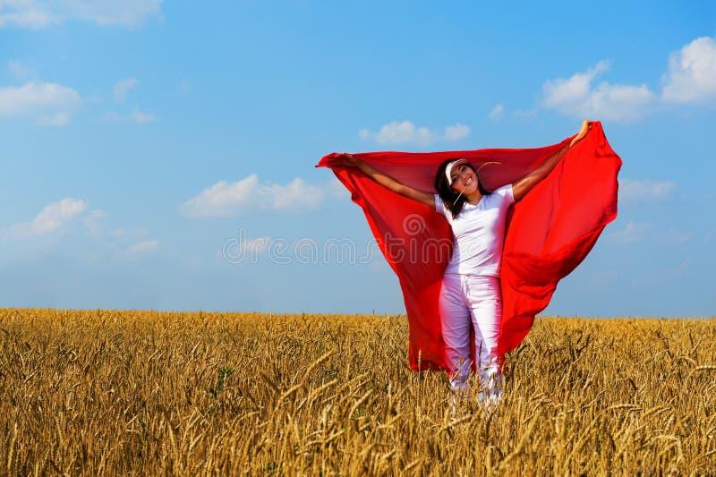 A menina de sorriso em um vestido branco e em um xaile vermelho imagens de stock