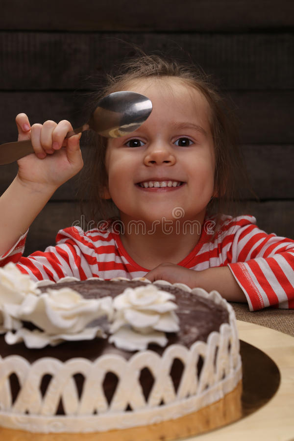 Menina de sorriso entusiasmado bonito com colher à disposição imagens de stock