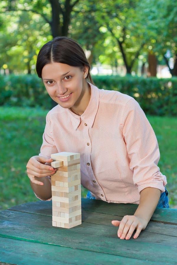 A menina de sorriso está jogando um jogo de madeira do bloco fotos de stock