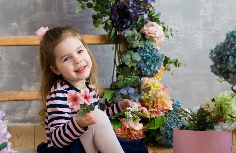 A menina de sorriso está sentando-se perto das escadas e do flowe de madeira fotos de stock royalty free