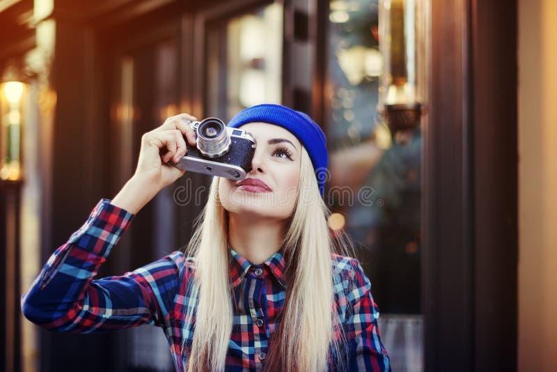 Menina de sorriso feliz à moda do moderno com a câmera retro velha do vintage Senhora que olha acima e que toma a imagem Estilo d imagens de stock royalty free