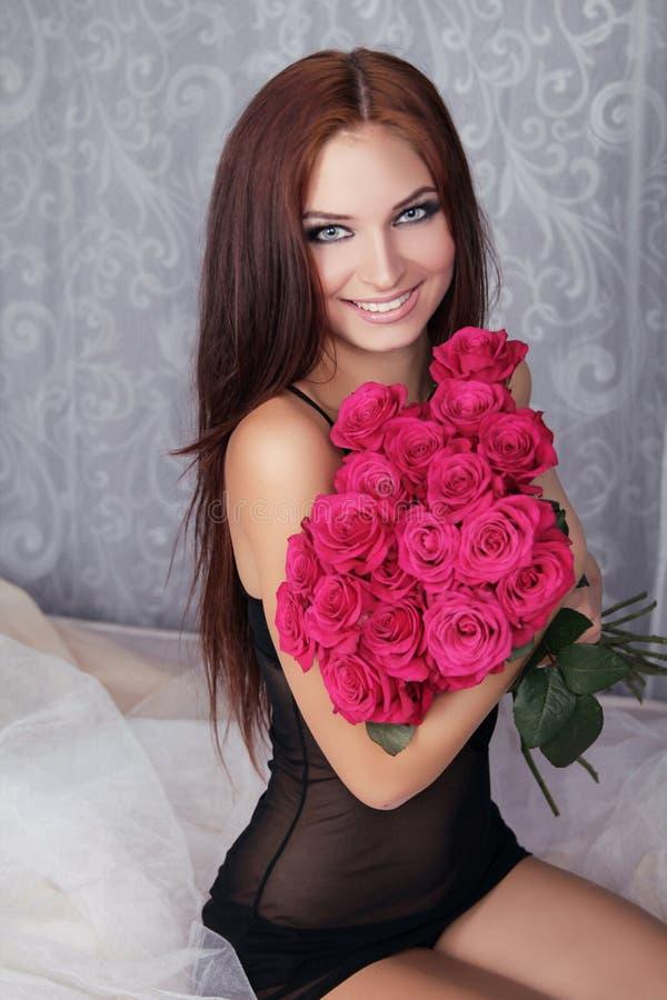 Menina de sorriso feliz bonita nova surpreendente com o ramalhete cor-de-rosa de foto de stock royalty free