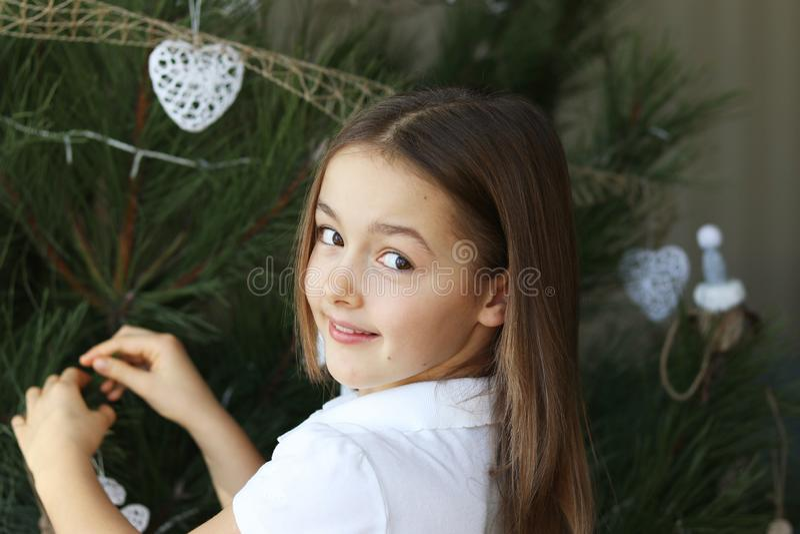 Menina de sorriso feliz bonita que decora a árvore de Natal com decorações brancas fotografia de stock royalty free