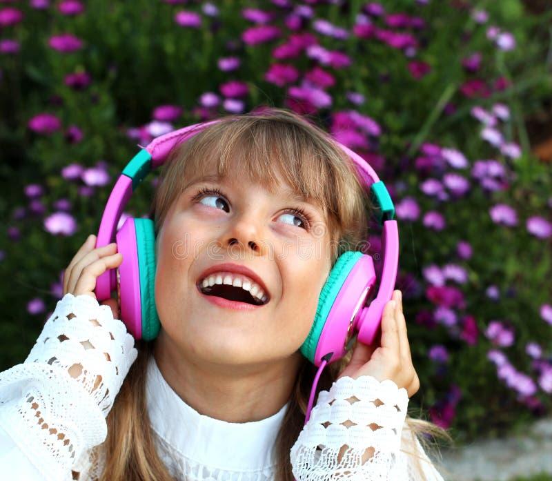 A menina de sorriso feliz com cabelo louro longo, laço veste a escuta a música em fones de ouvido em um fundo das flores da flor  imagem de stock royalty free