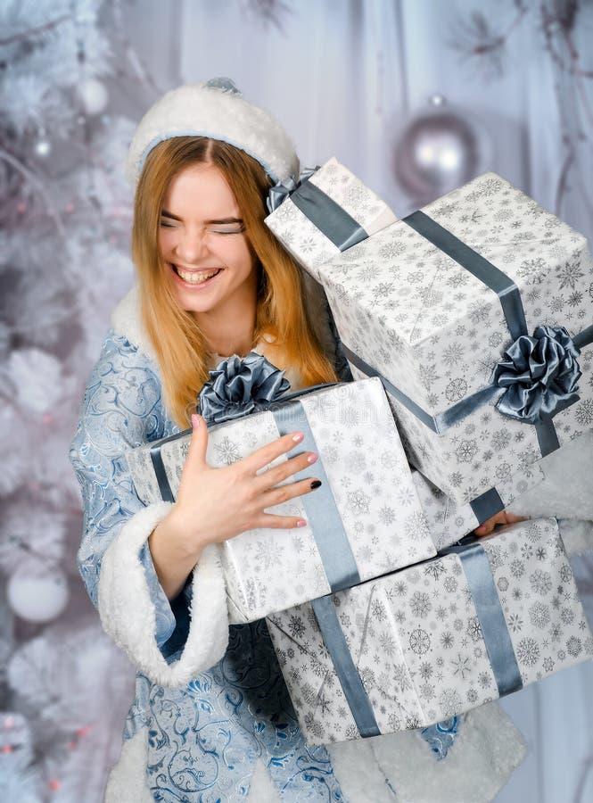 A menina de sorriso feliz com presentes em uma floresta nevado do inverno, neva donzela foto de stock royalty free