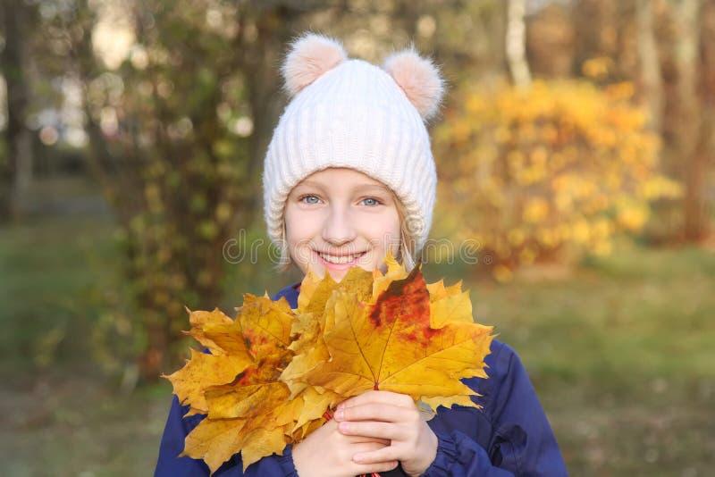 A menina de sorriso feliz da criança em um chapéu feito malha morno recolhe o ramalhete das folhas amarelas Outono no parque imagens de stock
