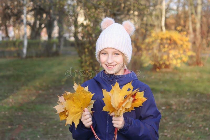 A menina de sorriso feliz da criança em um chapéu feito malha morno recolhe o ramalhete das folhas amarelas Outono no parque fotos de stock royalty free