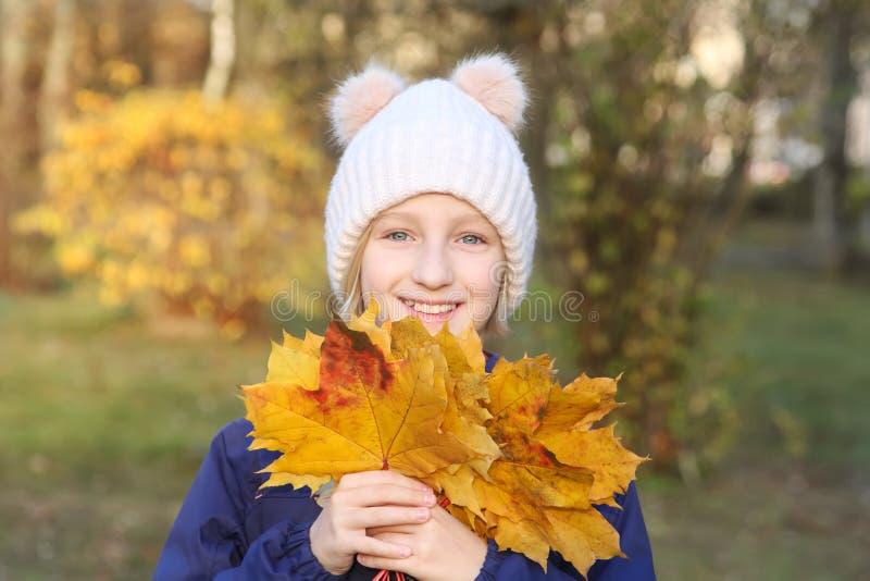 A menina de sorriso feliz da criança em um chapéu feito malha morno recolhe o ramalhete das folhas amarelas Outono no parque foto de stock royalty free