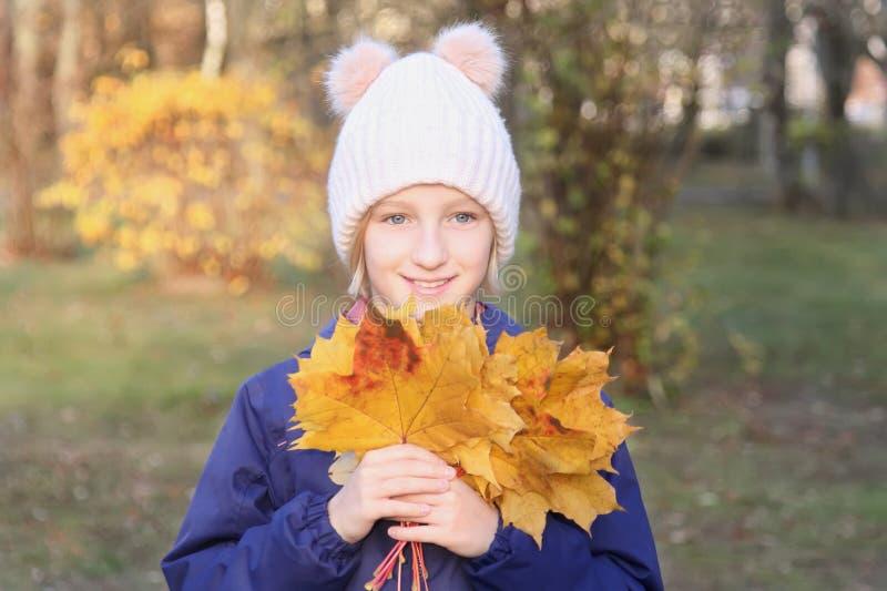 A menina de sorriso feliz da criança em um chapéu feito malha morno recolhe o ramalhete das folhas amarelas Outono no parque fotografia de stock