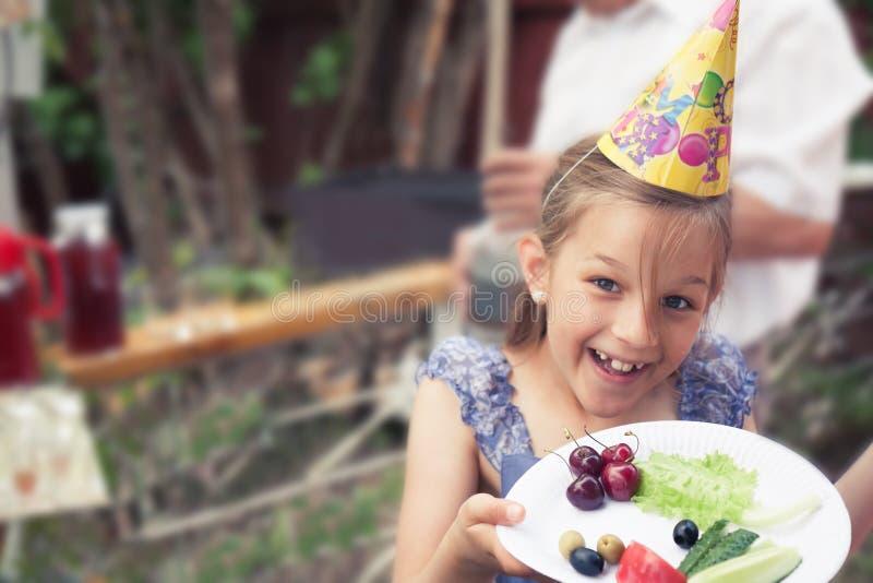 Menina de sorriso feliz da criança que trata comer saudável com a placa dos vegetais durante a festa de anos do pátio traseiro imagem de stock
