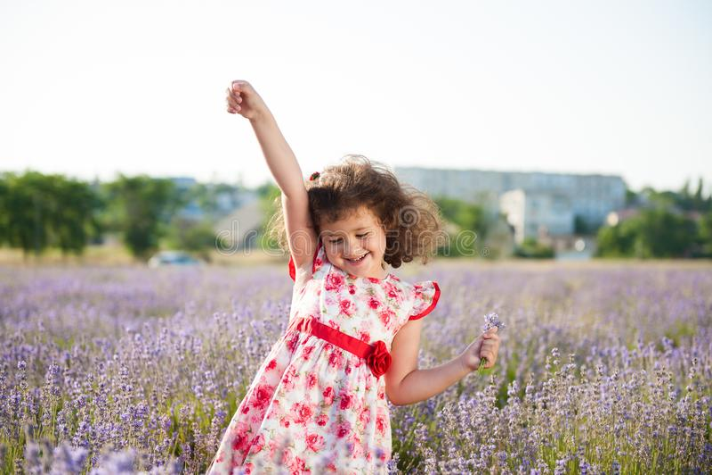 Menina de sorriso feliz deliciosa com o ramalhete das flores no campo da alfazema fotos de stock royalty free