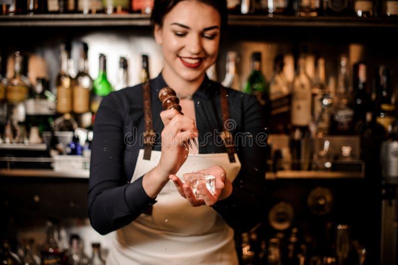 Menina de sorriso feliz do empregado de bar que esmaga uma parte de gelo para fazer a A.A. fotografia de stock