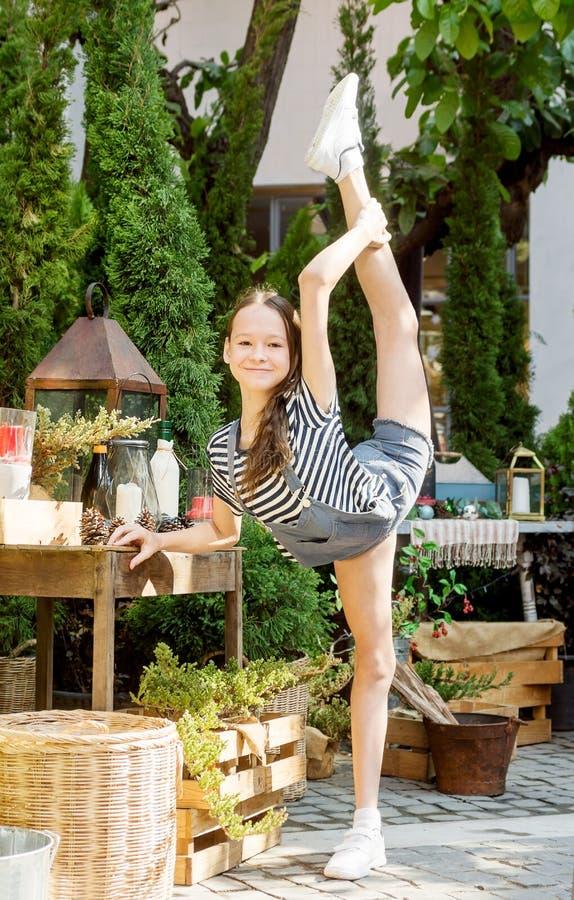 A menina de sorriso feliz do preteen faz a ginástica ao lado da tabela decorada do Natal entre árvores de cipreste em Tailândia A fotos de stock royalty free